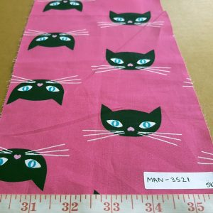 Cotton print fabric with cats or kitten faces printed on a pink base