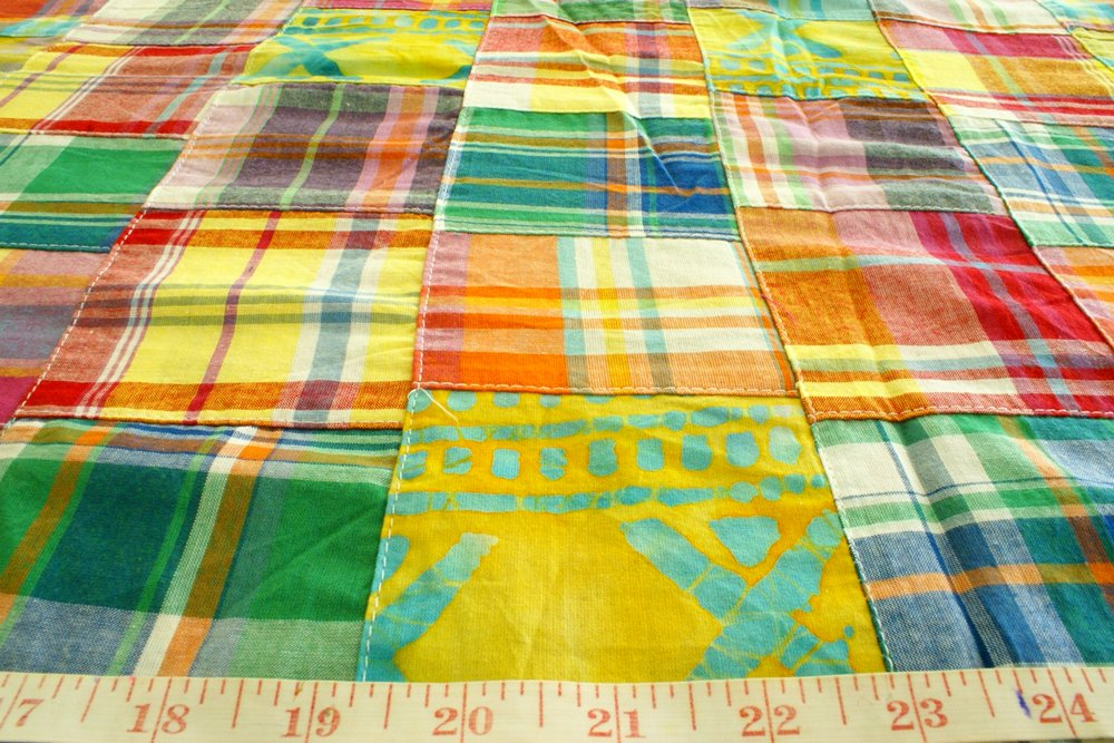 Patchwork printed fabric with patches of plaids and Batik prints, in cotton, ideal for children's wear, quilting and sewing projects, and crafts.